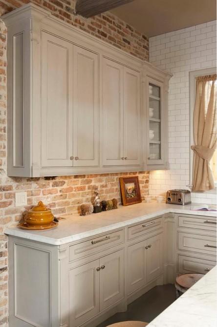 Meble kuchenne białe z cegłą na ścianie